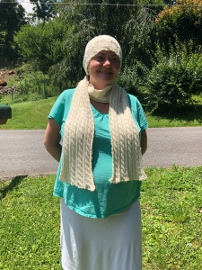Photo of me wearing the Palindrome Hat and Scarf with green trees in the background - The scarf and hat are off-white with cables and ribbing.